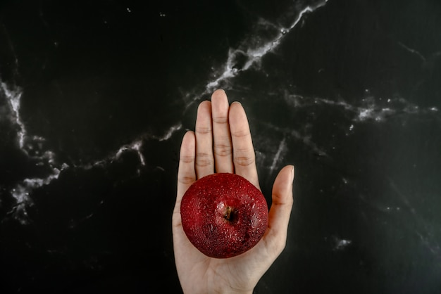 Hand holding fresh red apple with water spray droplets on apple over a black marble surface. top view flat lay composition.