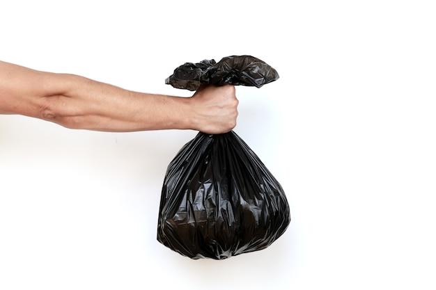 Рука держит полный мешок для мусора