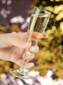 Hand holding full glass of bubbly champagne