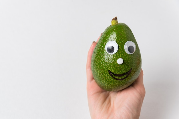 Hand holding funny avocado with googly eyes and smile. healthy food concept