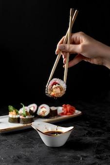Hand holding futo maki with chopstick on dark background.