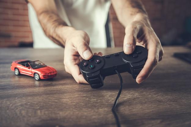 Рука, держащая контроллер игровой консоли, играет в гоночную игру