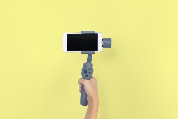 Hand holding gimbal or stabilizer with mobile phone on yellow pastel background