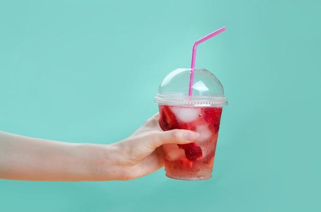 ピンクと緑の背景にイチゴカクテルのグラスを持っている手