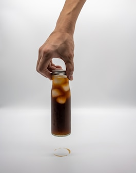 Hand holding a glass bottle of coffee with ice isolated on white