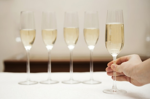 Hand holding a glass of champagne against row of glasses