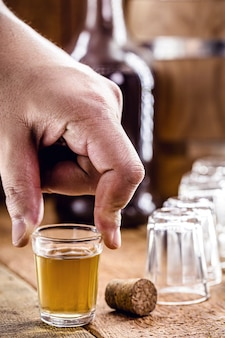 Hand holding glass of drips, sugar cane distilled beverage, in rustic wooden setting