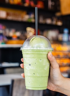 Hand holding glass of green tea frappe with ice cream