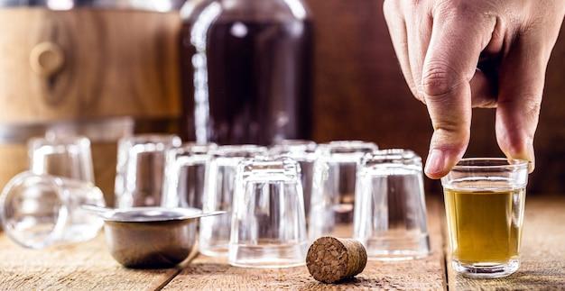 素朴な木製の設定で、滴りのガラス、サトウキビ蒸留飲料を手に持って