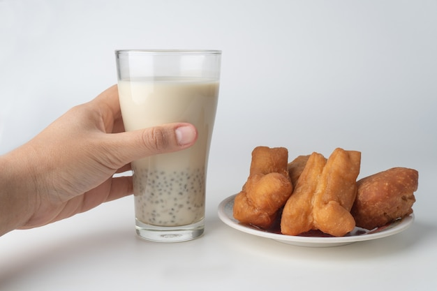 Hand holding glass of soy milk and doughnuts