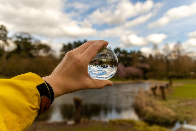 Hand holding a glass sphere in the nature