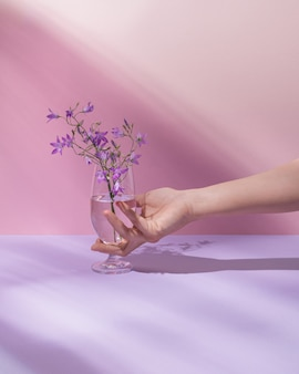 투명한 액체와 아름다운 보라색 들판 꽃이 있는 손을 잡고 유리. 파스텔 핑크 여름 또는 봄 배경입니다. 최소한의 자연, 미학. 자연적인 태양 광선과 그림자.