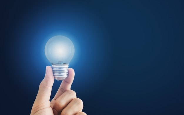 Hand holding glowing light bulb, on blue background