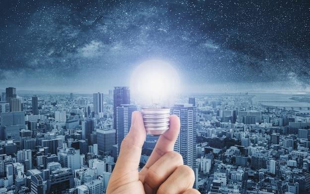 Hand holding glowing light bulb