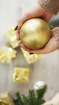 Hand holding gold ball decorations on christmas tree background.