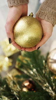 Hand holding gold ball decorations on christmas tree background