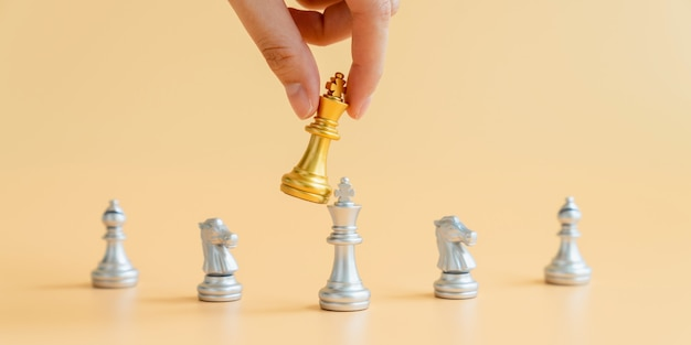 Hand holding gold chess king over silver chess king