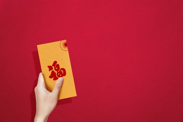 Hand holding gold envelopes (angpao) with a colored wall. happy chinese new year