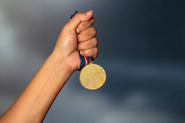 Hand holding gold medal on against cloudy sky