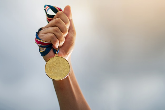 Hand holding gold medal on sky