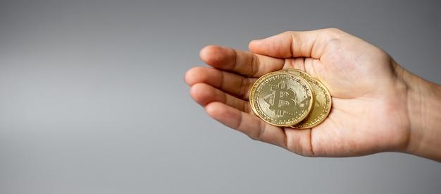 Рука, держащая золотую монету криптовалюты биткойн.