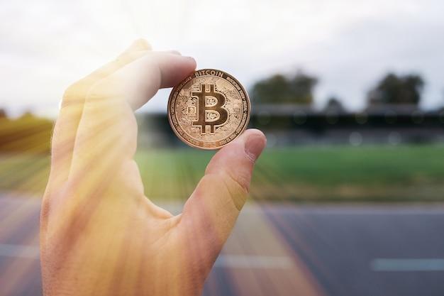 Hand holding golden bitcoin virtual money