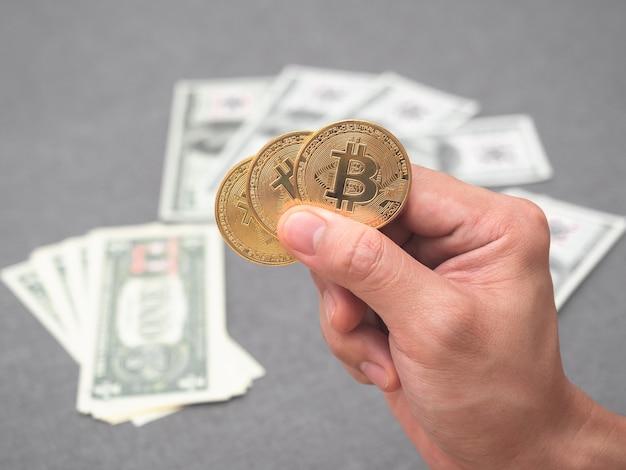 Рука, держащая золотой биткойн с денежным фоном концепции цифровых денег
