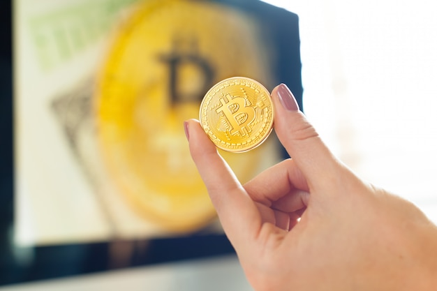 Hand holding golden bitcoin