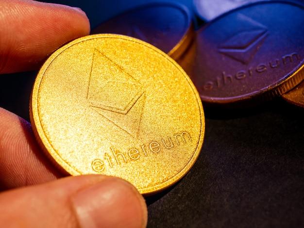 Рука, держащая золотую монету с символом эфириума. концепция цифровой валюты.