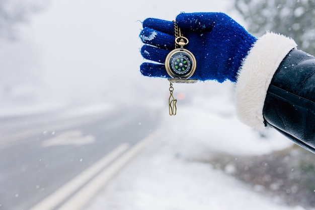 Hand holding golden compass on a road snowy landscape.
