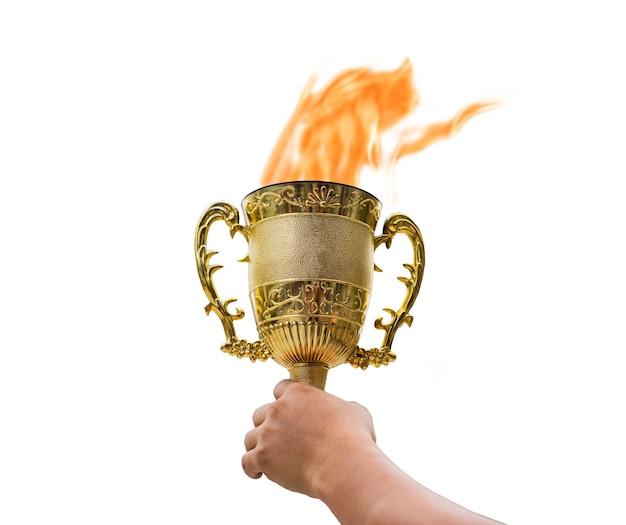 Рука держит золотой трофейный кубок со светящимся пламенем на белом фоне