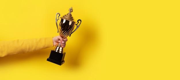 Hand holding golden trophy