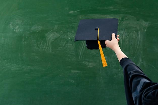Hand holding graduation hat on green chalkboard