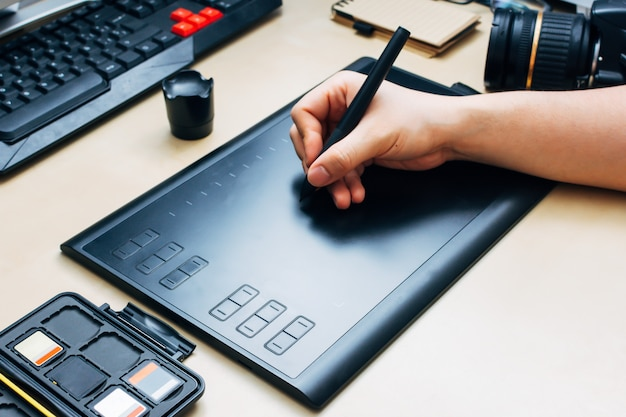 Hand holding graphic tablet pen and using it on a wooden desk next to a camera and memory cards