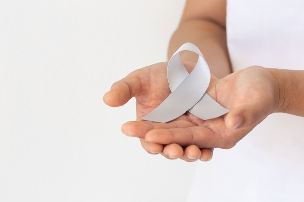 Hand holding gray ribbon on white fabric background. brain cancer awareness