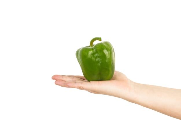 Hand holding a green bell pepper
