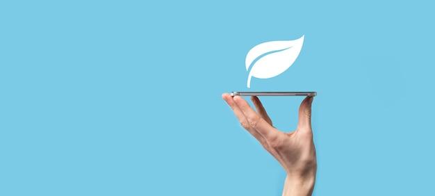 재생 가능하고 지속 가능한 개발을 위한 아이콘 에너지원이 있는 녹색 잎을 손에 들고 있습니다. 생태 개념입니다. 기술 생태 개념입니다.