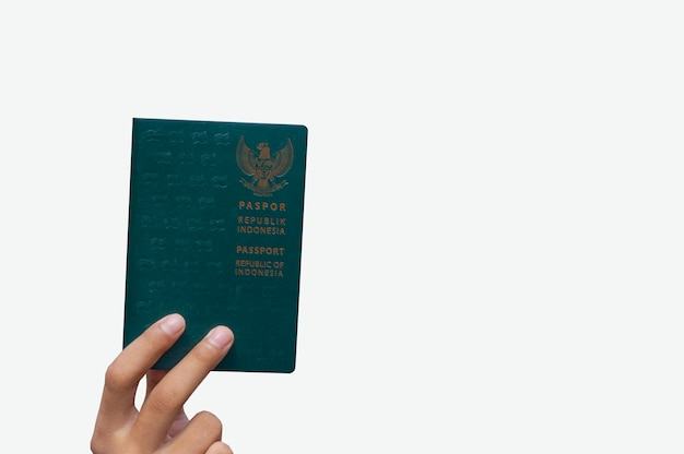 Hand holding green passport republic of indonesia isolated on white background