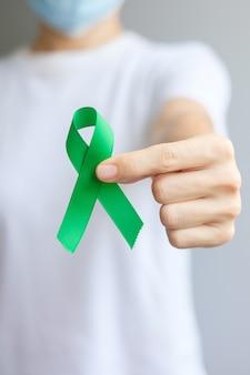 Рука держит зеленую ленту для печени, желчного пузыря, желчного протока, шейки матки, рака почек и месяца осведомленности лимфомы. концепция здравоохранения и всемирного дня рака