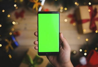 Hand Holding Green Screen Smartphone Above Christmas Decoration