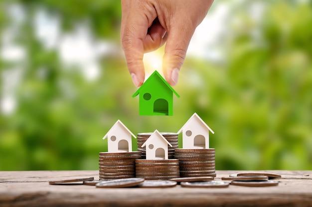 투자 부동산 개념 동전 더미에 놓인 녹색 작은 집 모델을 들고 있는 손