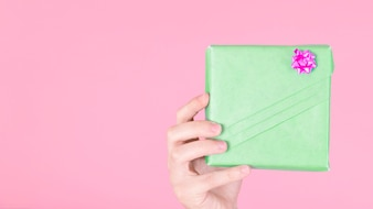 Hand holding green wrapped gift box with pink bow against colored background
