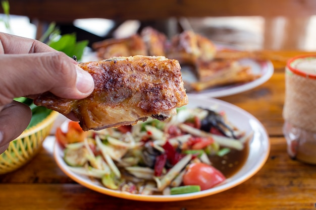 Hand holding the grilled chicken with papaya salad