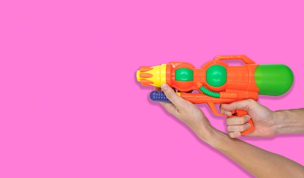 Hand holding gun water toy on pink background. free space for text