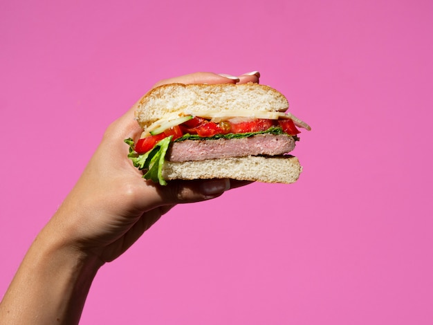 Hand holding half burger on pink background