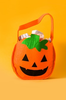 Hand holding halloween pumpkin bag with candies
