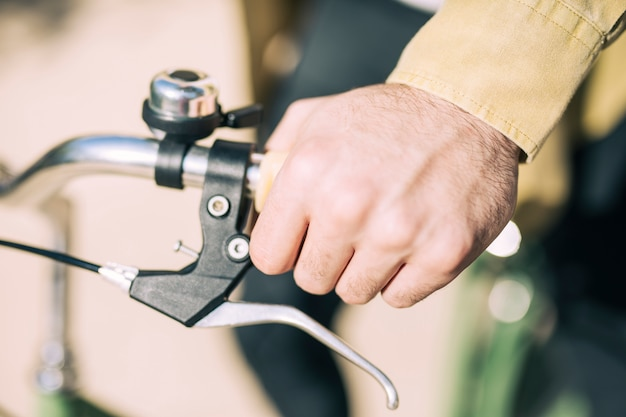 Hand holding a handlebars of a bicycle