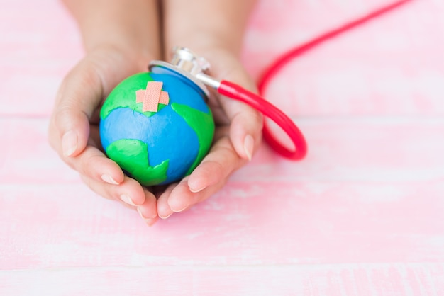 Hand holding handmade globe with red stethoscope on pink wooden background