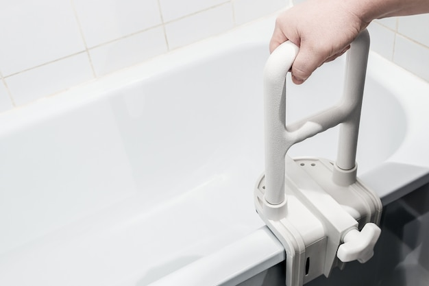Hand holding the handrail in the bathroom