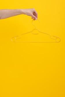 コピースペースのスタイリッシュなデザインで黄色の背景に分離された手持ちハンガーは、ファッションアクセスに見えます...
